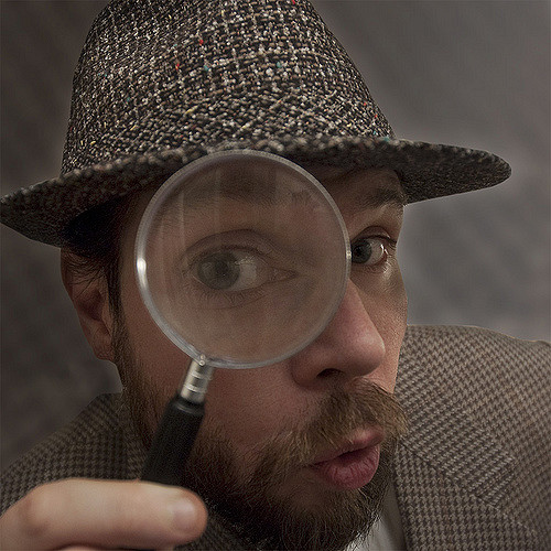 humorous pic of young man in mustache and beard with magnifying glass, dressed in brown plaid hayt and jacket