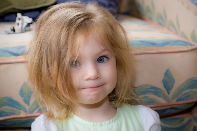 awful hair day for adorable strawberry blonde blue-eyed toddler, pastels and print in background