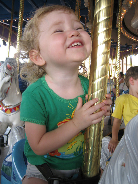 Adorable and very happy toddler on a merry-go-round. green shirt, gold pole